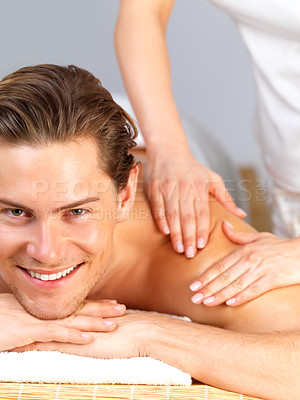 Buy stock photo Happy handsome man getting a back massage by female hands. Enjoying a holiday at the beauty spa. Looking into camera