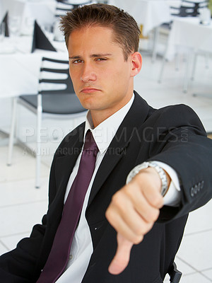 Buy stock photo A cocky businessman giving you a thumb's down with a frown
