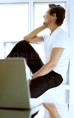 Buy stock photo A student taking a contemplative moment by his window. Nice laptop on a glass table.