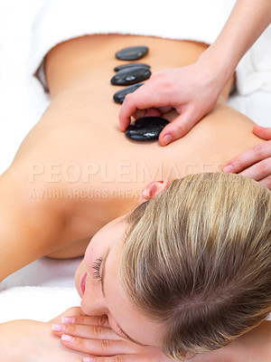 Buy stock photo Hot stones - Wellness and healthcare - Portrait of a beautiful young girl at the day spa with black stones on her bare back