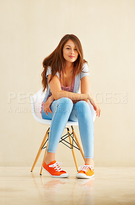 Buy stock photo Full length of young girl sitting in chair and giving you warm smile