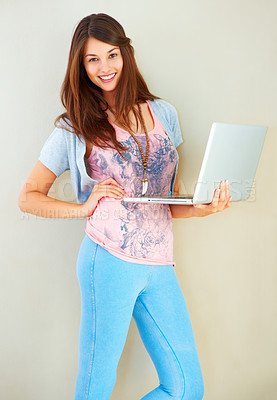 Buy stock photo Portrait of beautiful young girl standing with hand on waist and holding laptop