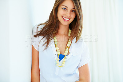 Buy stock photo Portrait of young woman standing against wall and giving you cute smile