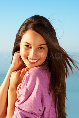 Buy stock photo Portrait of an excited young woman standing against sky and smiling