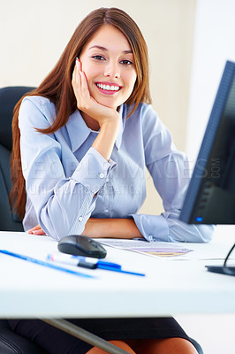 Buy stock photo Portrait of cute young female executive sitting at an office table and smiling
