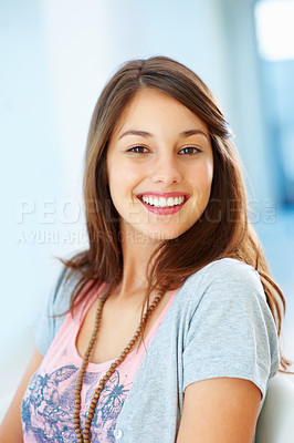 Buy stock photo Portrait of young woman sitting on chair and giving you beautiful smile
