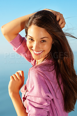 Buy stock photo Portrait of woman standing against sky with hand over head and giving you an attractive smile