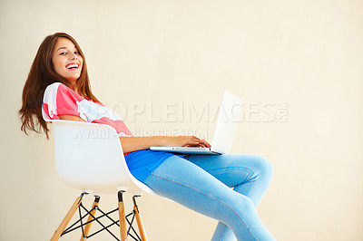 Buy stock photo Portrait of young woman relaxing on chair using laptop and giving you cute smile