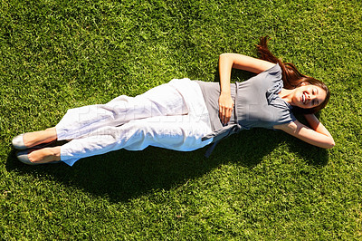 Buy stock photo Full length of pretty young woman resting on grass and smiling