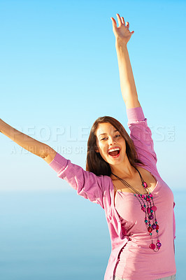 Buy stock photo Portrait of young woman raising arms against sky in joy