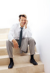 Relaxed young business man sitting on staircase