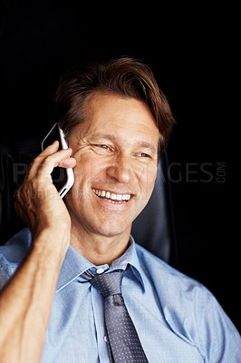Buy stock photo Portrait of a successful young businessman using mobile phone against black background