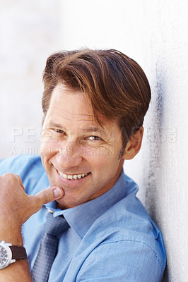 Buy stock photo Portrait of a handsome young male business executive leaning on white wall