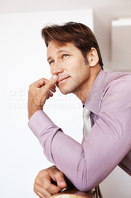 Buy stock photo Portrait of a young male executive lost in deep thought while leaning on railing