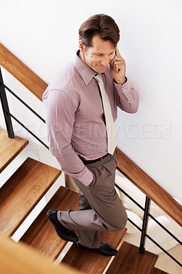 Buy stock photo Portrait of a young male entrepreneur walking down the stairs using cellphone