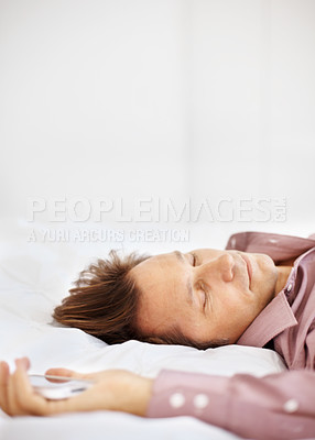 Buy stock photo Portrait of a male entrepreneur sleeping on bed with mobile phone in hand