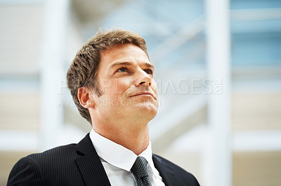 Buy stock photo Closeup of businessman looking upwards with a serious look