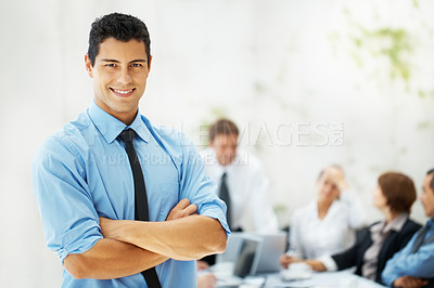 Buy stock photo View of executive with arms folded and colleagues in background