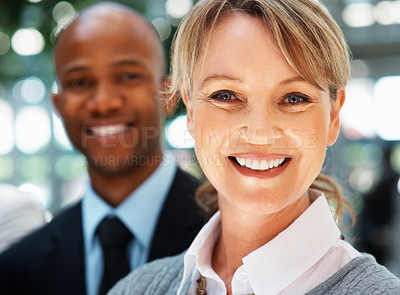 Buy stock photo Focus on pretty female executive with colleague in background