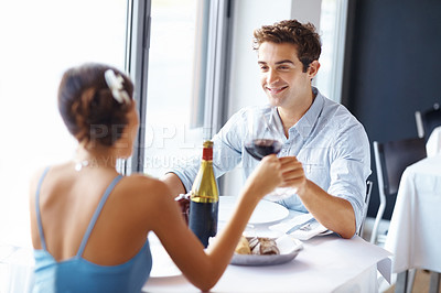 Buy stock photo Handsome young man toasting wine with his girlfriend at the restaurant smiling