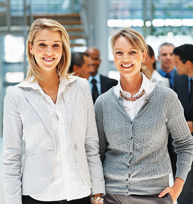 Buy stock photo Friendly female executives standing with group in background