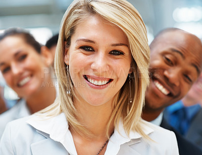 Buy stock photo Focus on pretty blonde executive with diverse colleagues behind her