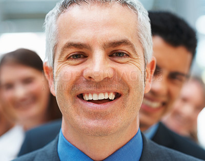 Buy stock photo Closeup of smiling businessman with colleagues in background