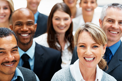 Buy stock photo Focus on pretty blond executive with colleagues around her