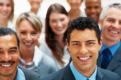 Buy stock photo Happy businessman smiling with team in background