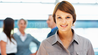 Buy stock photo Pretty young executive with colleagues in background