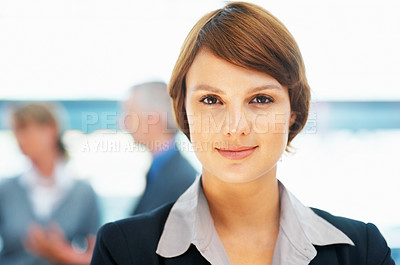 Buy stock photo Closeup of young female executive with colleagues in background