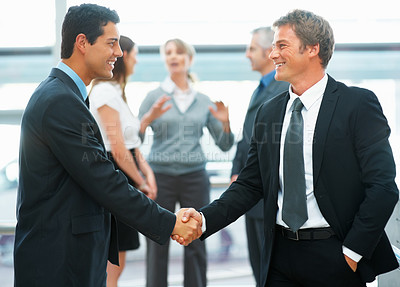 Buy stock photo Businessmen shaking hands with colleagues in background
