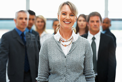 Buy stock photo Pretty businesswoman with team in background