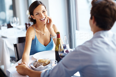 Buy stock photo Pretty young woman enjoying a lunch date with her boyfriend at a bright restaurant
