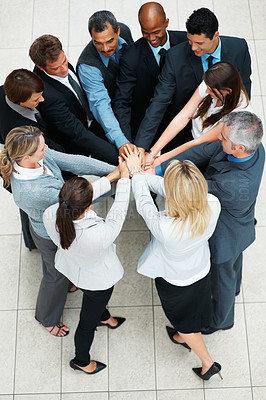 Buy stock photo Top view of colleagues placing their hands on top of one another