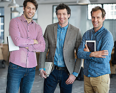 Buy stock photo Portrait of a group of male coworkers holding digital tablets while standing in an office