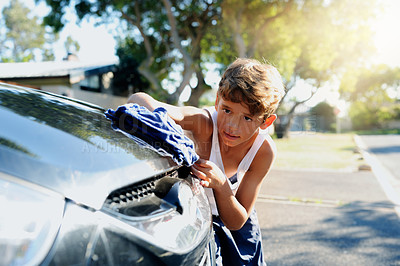 Buy stock photo Cropped shot of a young boy washing a car outside