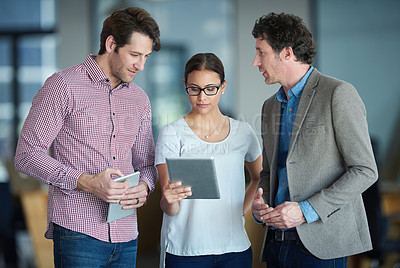 Buy stock photo Shot of three colleagues talking together over a digital tablet while standing in an office