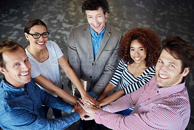 Buy stock photo Portrait of a group of smiling coworkers standing hand in hand in a huddle in an office