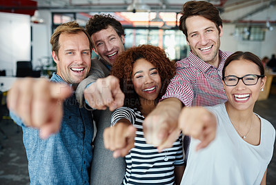 Buy stock photo Portrait of a group of smiling coworkers pointing at the camera while standing in an office