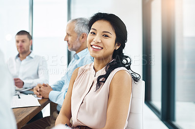 Buy stock photo Portrait of a young businesswoman sitting in a meeting with her colleagues in the background