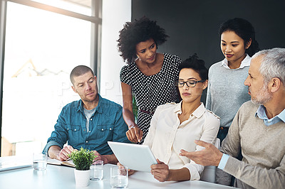 Buy stock photo Shot of a group of colleagues discussing something on a digital tablet together