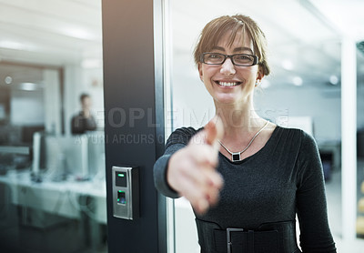 Buy stock photo Portrait of a young businesswoman offering you her hand while standing in an office doorway