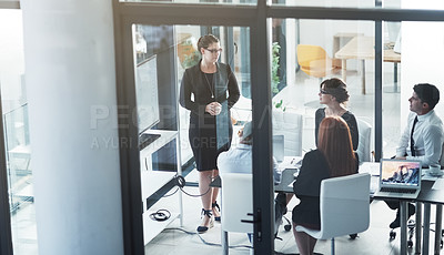 Buy stock photo Shot of an executive giving a presentation on a monitor to colleagues in a modern boardroom