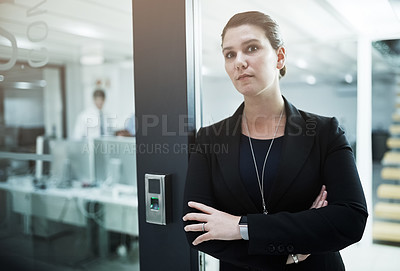 Buy stock photo Portrait of a young businesswoman standing with her arms crossed in an office doorway