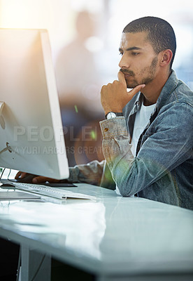 Buy stock photo Shot of a young designer deep in thought while working on a computer in a modern office