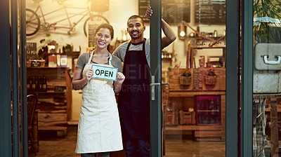Buy stock photo Portrait of a young man and woman holding up an open sign in their store