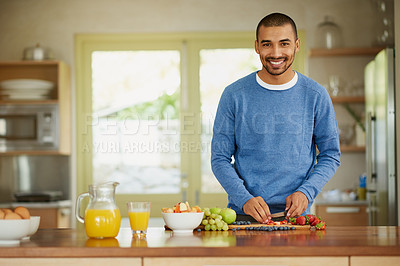 Buy stock photo Portrait of a happy young man preparing a healthy snack at home