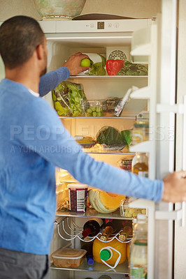 Buy stock photo Rearview shot of a man opening a fridge filled with healthy food at home