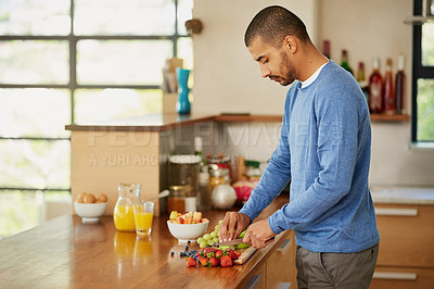 Buy stock photo Shot of a young man preparing a healthy snack at home